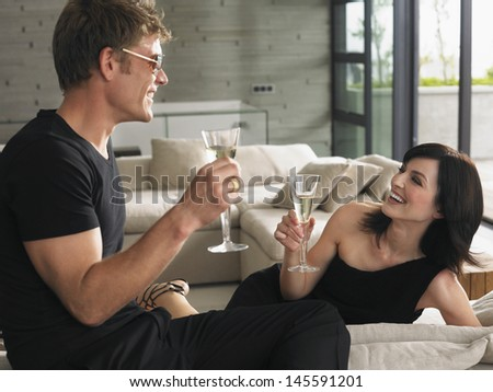 Young man and woman drinking champagne in the living room at resort - stock photo