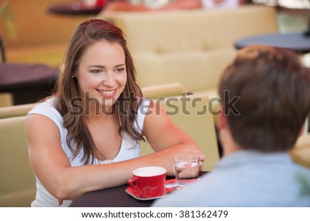 Young man and woman drinking coffee outdoor and having a chat - stock photo