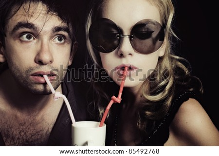 Young man and woman drinking through a tube - stock photo