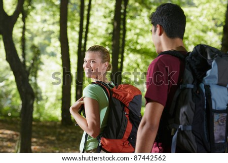 young man and woman during hiking excursion, with woman looking over shoulders. Horizontal shape, rear view, waist up - stock photo