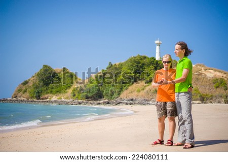 Young man and woman  embraces on tropical beach with lighthouse on back - stock photo