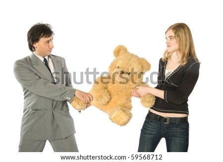 Young man and woman fighting over a teddy-bear - stock photo