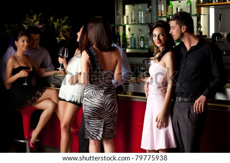 young man and woman flirting beside bar in a club - stock photo