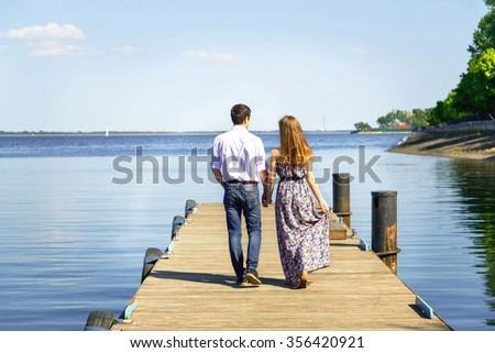 Young man and woman goes hand in hand on pier - stock photo