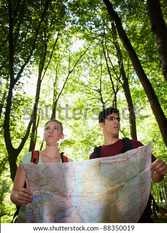 young man and woman got lost during hiking excursion and look for destination on map. Vertical shape, waist up - stock photo