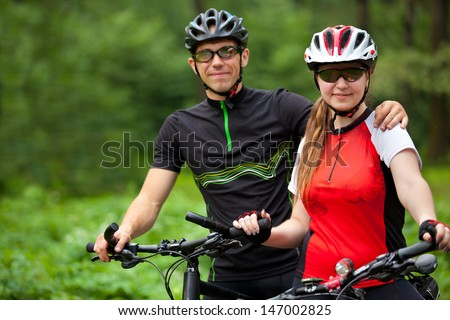 Young man and woman having bike ride in nature