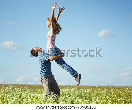 Young man and woman having fun on countryside meadow with herbs and flowers