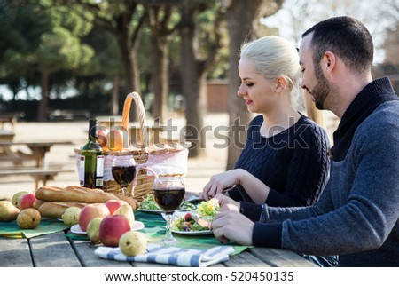 Young man and woman having picnic in sunny spring day at countryside
