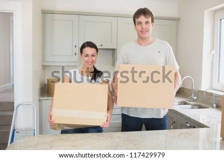 Young man and woman holding moving boxes in kitchen - stock photo