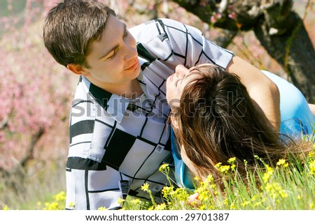 young man and woman in green grass ready to kiss