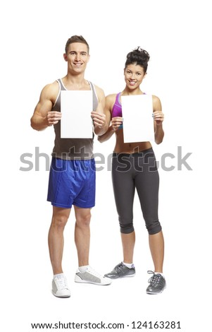 Young man and woman in sports outfits on white background smiling with blank cards - stock photo