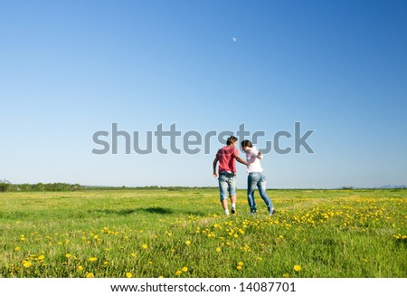 Young man and woman jumping over green field - stock photo