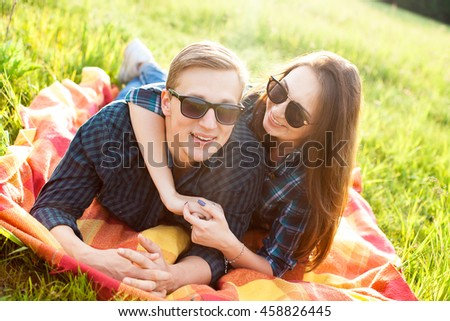 Young man and woman lie outdoors in the sunlight
