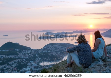 Young man and woman on a beautiful sunset background