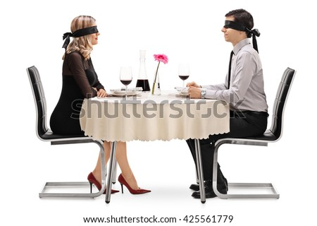 Young man and woman on a blind date seated at a restaurant table isolated on white background - stock photo