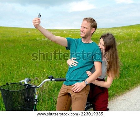 young man and woman on bicycle take a selfie - stock photo