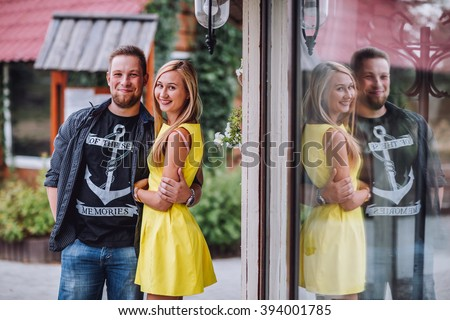 Young man and woman on the nature. Playful couple in love. Blonde in a yellow dress and a guy in a T-shirt . - stock photo