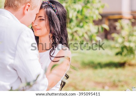 Young man and woman on the nature. Playful couple in love. Woman in white dress. Man in white jacket
