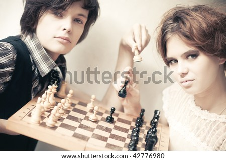 Young man and woman playing chess. Soft yellow tint. - stock photo