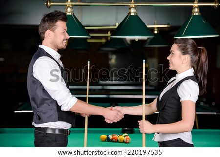 Young man and woman playing professional billiards in the dark billiard club - stock photo
