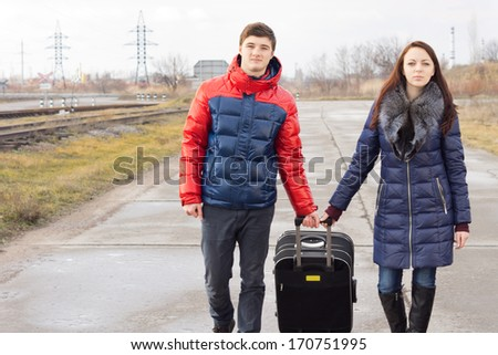 Young man and woman pulling along a suitcase as they walk together along a country road alongside a railway line - stock photo