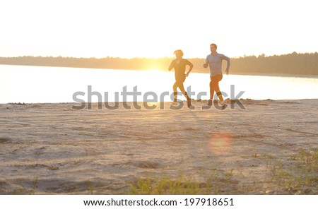 Young man and woman running along the waterfront in sunshine - stock photo