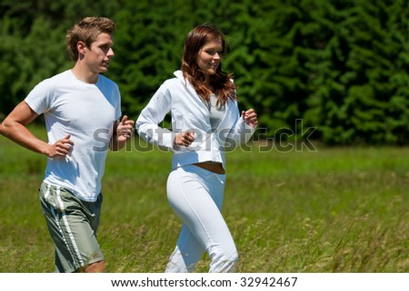Young man and woman running outdoors on a sunny day, shallow DOF - stock photo