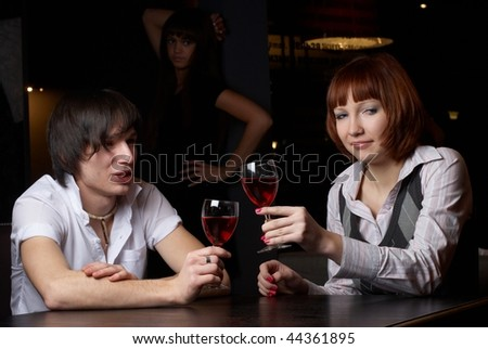 Young man and woman sitting in cafe - stock photo