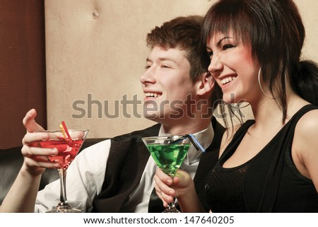 young man and woman sitting on a sofa and holding a glass - stock photo