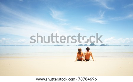 Young man and woman sitting on sand by sea and looking to somewhere - stock photo