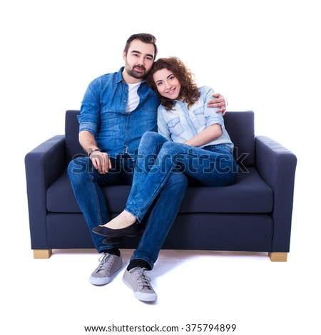young man and woman sitting on sofa isolated on white background - stock photo