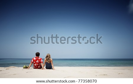 Young man and woman sitting on warm sand at sunny day and looking to somewhere - stock photo