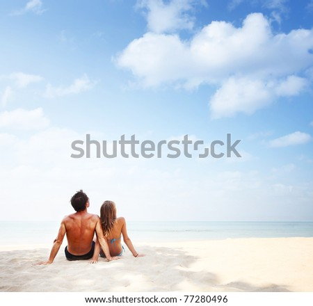 Young man and woman sitting on warm sand by a sea and looking to somewhere - stock photo