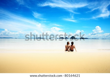 Young man and woman sitting on wet yellow sand of a tropical resort
