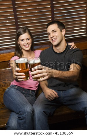 Young man and woman sitting together toasting their beers at pub looking at viewer. Vertical shot. - stock photo