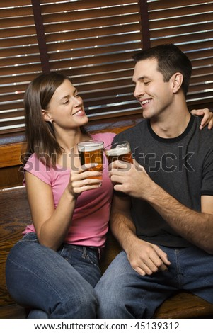 Young man and woman sitting together toasting their beers while relaxing at a pub. Vertical shot. - stock photo