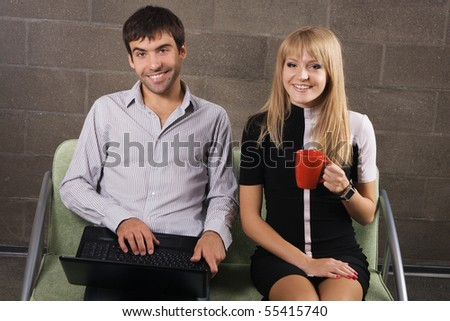 Young man and woman sitting with a laptop indoors