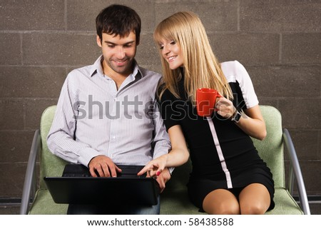 Young man and woman sitting with a laptop indoors - stock photo