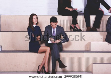 Young man and woman skilled managers are listening to lectures at the Graduate School of Business for Professionals. Two smarts internationals students are waiting the beginning of exam at university - stock photo