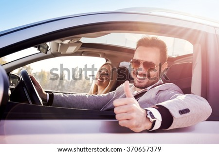 Young man and woman smile at the camera while seated in a new car. Couple buying a car. - stock photo