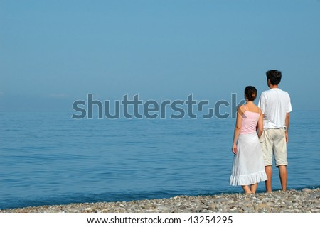 Young man and woman standing embraced on the beach