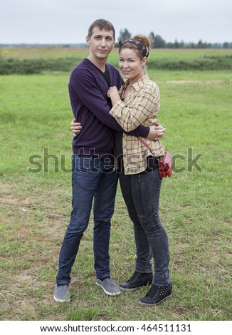 Young man and woman standing on the green grass in countryside