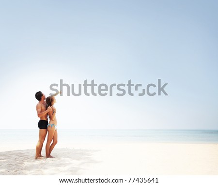 Young man and woman standing on warm sand at sunny day and enjoying each other