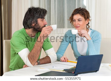 Young man and woman take a break from studying in front of the computer to have some coffee and a chat.