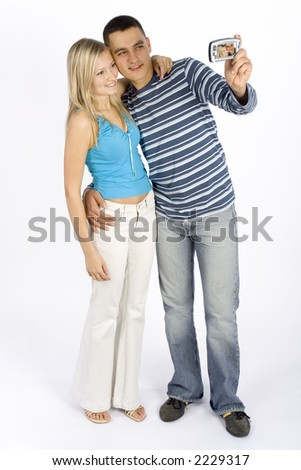 young man and woman taking picture by phone/palmtop - stock photo