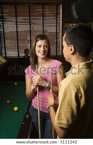 Young man and woman talking and smiling while playing billiards. - stock photo