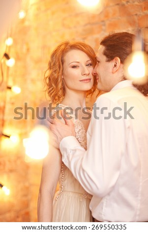 Young man and woman together over brick red wall and lights
