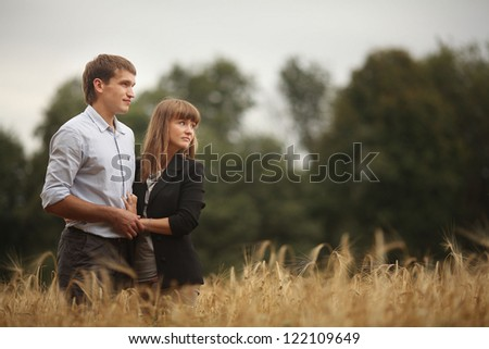 young man and woman walking in a field of wheat - stock photo