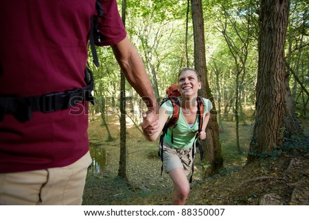 young man and woman walking in woods, with man helping his girlfriend. Horizontal shape, three quarter length - stock photo
