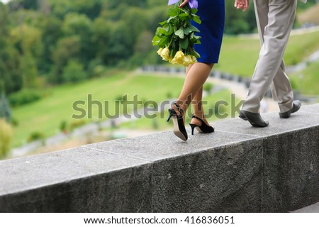 Young man and woman walking on a parapet wall. Yellow roses in hands at the girl. The woman is behind the man. Step by step. Hill, the park in the background. - stock photo